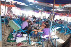 Thai family eating lunch seated at beach Stock Image