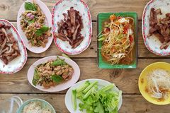 Thai favorite menu papaya `Som-Tum`. Serve with grilled pork on wooden table royalty free stock images