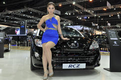 A Thai female presenter next to a Peugeot RCZ Royalty Free Stock Photos