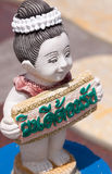 A Thai figure holds signpost Royalty Free Stock Photo