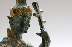 Thai Figurine of Lute Playing Deity. Close-up of a Thai figurine Royalty Free Stock Photos