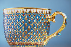 Thai fine art traditional five colors (Bencharong) tea cup over blue blurry background. Royalty Free Stock Photography