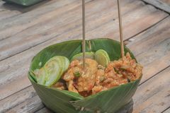 Thai Fish Cake. Thai fried fish cake served with sweet chilli sauce  in banana leaf container stock images