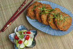 Thai Fish Cakes - Tod Mun. A plate of Thai fish cakes with Thai cucumber salsa and red chopsticks stock photos