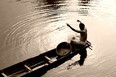 Thai Fisherman in Boat. Small fishing boat holds a Thai man with his fishing gear.  Water ripples out from boat's edge while man prepares his line.  Image is Stock Image