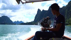 Thai fisherman driving the long tail boat with a big engine. Thai fisherman driving the long tail boat with a big motor engine. Cheow Lan lake. Khao Sok stock video footage