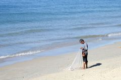 Thai fisherman with fishnet on Ao Nang beach Royalty Free Stock Images