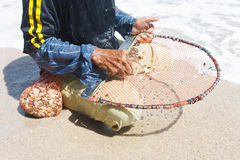 A thai fisherman is searching for shells Royalty Free Stock Photo