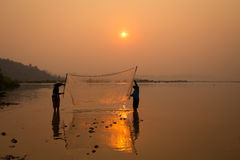 Thai fisherman silhouette in sunrise landscape Mekong river are. Catching fish together with friend. Is life`s thai and Laos people`s Fisherman of Mekong river royalty free stock image