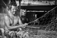 Thai fishermen mending his fishing net in Thailand Stock Image