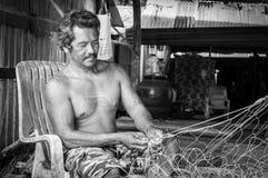 Thai fishermen mending his fishing net in Thailand Stock Photography