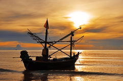 Thai Fishing Boat at Sunshine. A fishing boat silhouette against a glorious orange sunshine on the ocean. Hua-Hin : Thailand Royalty Free Stock Images