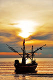 Thai Fishing Boat at Sunshine. A fishing boat silhouette against a glorious orange sunshine on the ocean. Hua-Hin : Thailand Royalty Free Stock Image