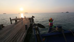 Thai fishing boat and wooden catwalk on the sea coast during sunset. Travel. stock video
