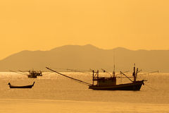 Thai fishing boats at sunset. Traditional fishing boats on the Andaman Sea in Thailand at sunset Royalty Free Stock Image