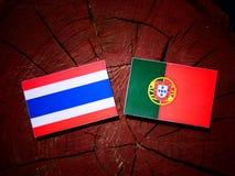 Thai flag with Portuguese flag on a tree stump isolated. Thai flag with Portuguese flag on a tree stump royalty free illustration
