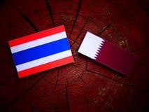 Thai flag with Qatari flag on a tree stump isolated Royalty Free Stock Image