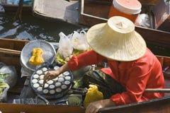 Thai Floating Market. Thai woman cooking and selling food at floating market near Bangkok, Thailand Stock Photo