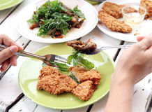 Thai food. Closeup image of man eating Thai food, fried shrimp cake and fried roast duck with basil stock photography