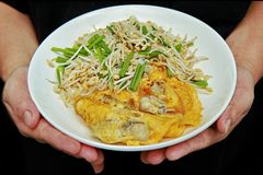 Thai food,Fried egg and oyster with bean sprouts and shallot as. Fried oyster with bean sprouts and shallot as `Hoi Tod` in Thai served with chili sauce is Royalty Free Stock Images