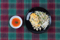 Thai food,Fried egg and oyster with bean sprouts and shallot as Hoi Tod Khai in Thai served with chili sauce. Royalty Free Stock Image