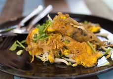 Thai food, Fried mussel with egg and bean sprouts in plate on wooden table. In the restaurant stock images