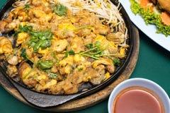 Thai food, fried mussel pancake in hot pan Stock Photos