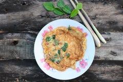 Thai food menu, fried omelette, herbs, add basil, onion, red pepper, lemongrass, kaffir lime leaves in a red dish. Thai food menu fried omelette herbs add basil royalty free stock photo