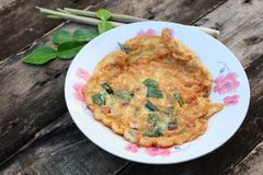 Thai food menu, fried omelette, herbs, add basil, onion, red pepper, lemongrass, kaffir lime leaves in  red dish wooden background. Thai food menu fried omelette royalty free stock image