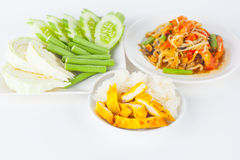 Thai food. Papaya salad (som tum Thai) with sticky rice and grilled chicken on white paper background Royalty Free Stock Photo