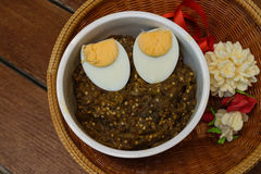 Thai food pound eggplant with boiled egg on wood table Royalty Free Stock Photos