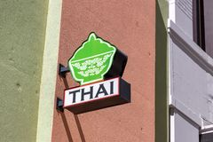 Thai food restaurant sign mounted on a subtle but colorful painted building wall. Thai food restaurant sign mounted on building wall stock images