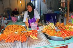 Thai Food for Sale, Thailand. Old lady in fastfood vendor selling traditional thai foods, chicken and pork specialities to customers. Phuket town during weekend Royalty Free Stock Image