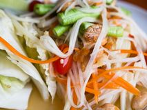 Thai food, Som Tam. Papaya salad with dried shrimps, peanuts, string beans, chili pepper and lime. Very shallow depth of field with the nearest part in focus Royalty Free Stock Photo