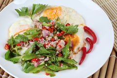 Thai food,Spicy wing bean with pork topped fried egg. Royalty Free Stock Photo