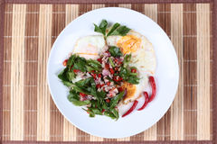 Thai food,Spicy wing bean with pork topped fried egg. Stock Photos