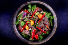 Thai Food - Stir fried Pork liver with goat pepper, sweet pepper, scallion and celery on hot plate Royalty Free Stock Image