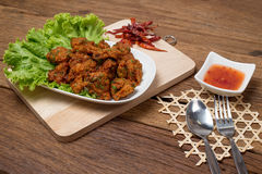 Thai Food Thai Fried Fish Cake Called Tod Mun Pla on wood background. Thai fried fish cake (Tod Mun Pla) or prawn fritter ball with dipping red sauce and spoon Stock Images