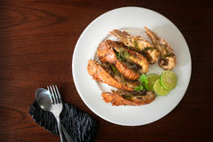 Thai Foods : stir-fried rock lobster with chilli, garlic and Tha. I herbs roasted on frying pan on dark background Kang Pad Kratiem Prik sod Royalty Free Stock Photos