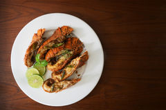 Thai Foods : stir-fried rock lobster with chilli, garlic and Tha. I herbs roasted on frying pan on dark background Kang Pad Kratiem Prik sod Royalty Free Stock Photography