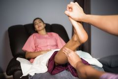Thai foot massage to Asian woman in spa. Foot and leg Thai massage to attractive Asian tan woman on sofa in spa. Health care and Relax to heal pain concept stock photos
