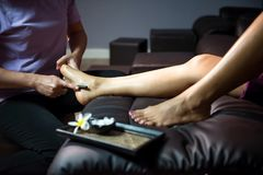 Thai foot massage by wooden stick. Thai original foot massage by wooden stick tool to tanned woman on sofa. Foot Aroma leg spa treatment by oil and cream. Health Royalty Free Stock Photography