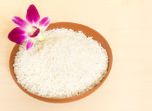 Thai Fragrant Jasmine Rice in a Brown Ceramic Bowl garnish with. Thai Fragrant Jasmine Rice in Brown Ceramic Bowl garnish with Orchid Flower on Wood Table Royalty Free Stock Image