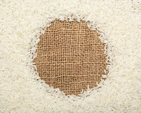Thai fragrant jasmine rice. Forming a round frame on burlap fabric Royalty Free Stock Image