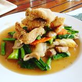 Thai fried noodle with fish and vegetable. Thai fried noodle with crispy fish and vegetables; Chinese kale, carrot and mushroom Stock Photos