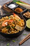 Home Made Pad thai with Shrimp and Vegetables on Marble table. Thai Fried Noodles and Seasoning with Lemon There is a brown paper to tag the word THAILAND. and stock photo