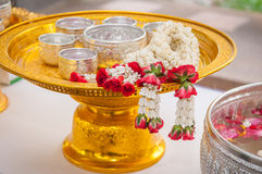 Thai garland Flowers. And Water with jasmine and roses corolla in bowl on golden tray (Use for Songkran festival in Thailand Stock Photos