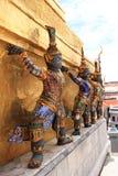 Thai giant stand around gold pagoda Royalty Free Stock Image