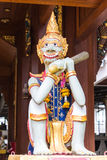 Thai giant statue with teak chapel Royalty Free Stock Image