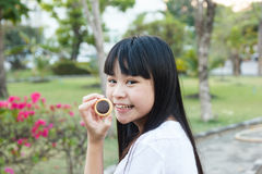 Thai girl eating chocolate cookie. Thai girl eating chocolate cookie at garden Royalty Free Stock Images